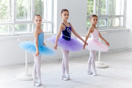 Three little ballet girls in multicolored tutu posing at ballet barre together on white background