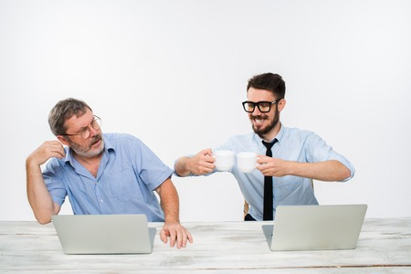 bad news: The two colleagues working together at office on white  background. The old man getting bad news. the young man is smiling. concept of competition in business
