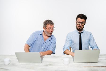 オフィスで一緒に働いている 2 人の同僚はホワイト バック グラウンドです。彼らは何かを議論します。両方が 1 つのコンピューターの画面を見てい