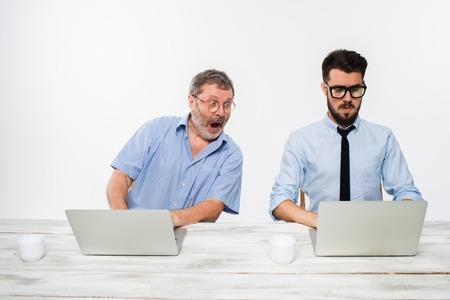 celos: Los dos colegas que trabajan juntos en la oficina en el fondo blanco. Ellos discutiendo algo. ambos est�n buscando en una pantalla de ordenador. concepto de competencia en los negocios y los celos Foto de archivo