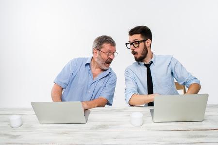 celos: Los dos colegas que trabajan juntos en la oficina en el fondo blanco. ambos est�n mirando a la pantalla del ordenador adyacente. concepto de competencia en los negocios y los celos