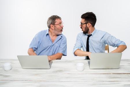 dois: Os dois colegas que trabalham juntos no escritório no fundo branco. Eles surpreenderam olhando para o outro Imagens