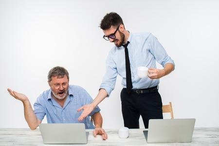 celos: Los dos colegas que trabajan juntos en la oficina en el fondo blanco. El anciano recibiendo malas noticias. el joven es feliz. concepto de competencia en los negocios y los celos