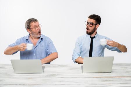 surprised: Los dos colegas que trabajan juntos en la oficina en el fondo blanco. Se sorprendi� mirando el uno al otro y el consumo de caf� Foto de archivo