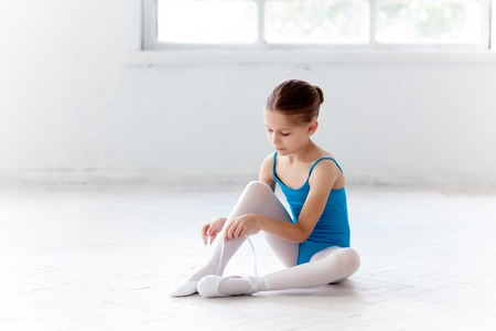 sit studio: Beautiful little ballerina in blue dress for dancing sitting on the floor and puting on foot pointe shoes on white ballet studio background