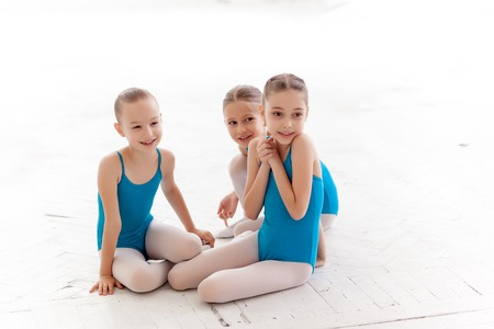 little girl dancing: Three little ballet girls sitting in blue swimsuit and pointe shoes together on white background in ballet studio
