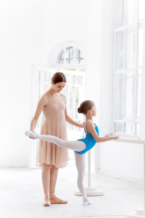 rehearsal: The little ballerina in tutu with personal classic ballet teacher in dance studio posing at ballet barre on a white studio background