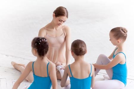 ballet: Tres peque�as bailarinas con el maestro de ballet personal en el estudio de danza. bailarina de ballet cl�sico como profesor que se sientan en un estudio blanco Foto de archivo