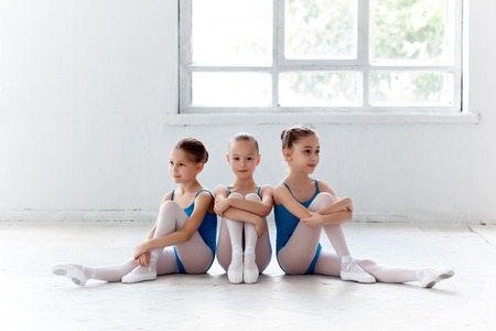 Three little ballet girls sitting in blue swimsuit and pointe shoes together on white background in ballet studio