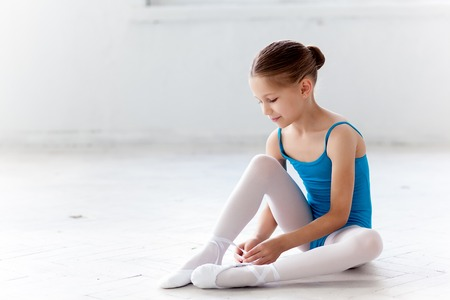 pretty feet: Beautiful little ballerina in blue dress for dancing sitting on the floor and puting on foot pointe shoes on white ballet studio background
