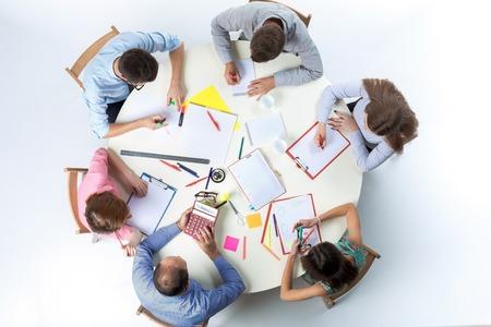 Vista dall'alto del business team, seduto a una tavola rotonda su sfondo bianco. concetto di successo del lavoro di squadra Archivio Fotografico
