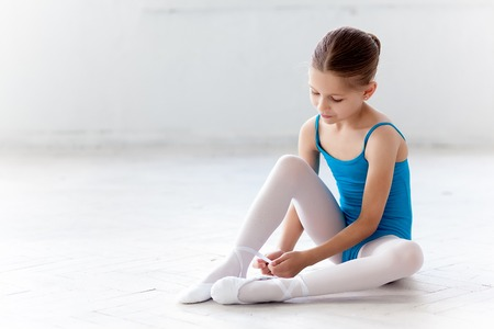 little girl dress: Beautiful little ballerina in blue dress for dancing sitting on the floor and puting on foot pointe shoes on white ballet studio background