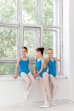 Three little ballet girls standing in blue swimsuit together in white ballet studio