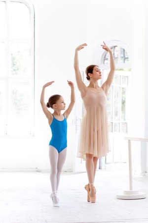 De kleine ballerina in tutu met persoonlijke klassieke ballet leraar poseren samen op een witte achtergrond dansstudio Stockfoto