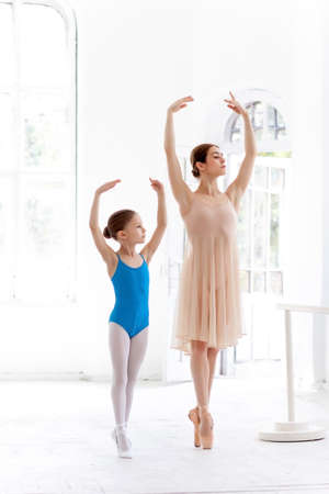 The little ballerina in tutu with personal classic ballet teacher posing together on a white dance studio background 免版税图像