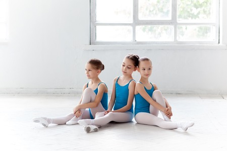 little models: Three little ballet girls sitting in blue swimsuit and pointe shoes together on white background in ballet studio