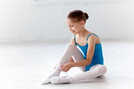 little girl sitting: Beautiful little ballerina in blue dress for dancing sitting on the floor and puting on foot pointe shoes on white ballet studio background