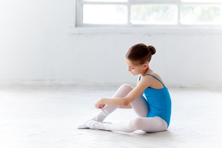 Beautiful little ballerina in blue dress for dancing sitting on the floor and puting on foot pointe shoes on white ballet studio background