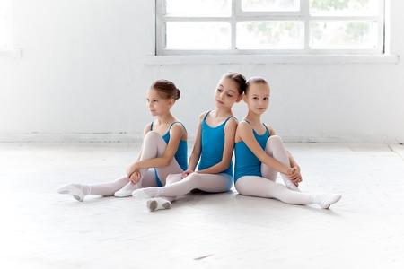 ni�as peque�as: Tres ni�as de ballet que se sientan en traje de ba�o azul y zapatos de punta juntos en el fondo blanco en el estudio de ballet Foto de archivo