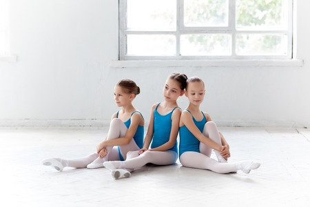 little girl swimsuit: Three little ballet girls sitting in blue swimsuit and pointe shoes together on white background in ballet studio
