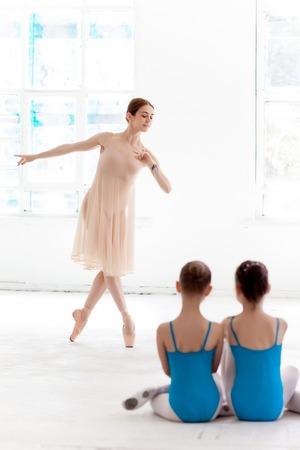ballet clásico: Dos pequeñas bailarinas con el maestro de ballet personal en el estudio de danza. bailarina de ballet clásico como profesor posando sobre un fondo blanco. en primer plano las niñas espalda Foto de archivo