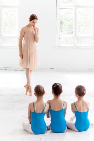 ballet niñas: Tres pequeñas bailarinas con el maestro de ballet personal en el estudio de danza. bailarina de ballet clásico como profesor posando sobre un fondo blanco Foto de archivo