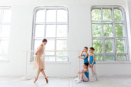 ballet ni�as: Tres peque�as bailarinas con el maestro de ballet personal en el estudio de danza. bailarina de ballet cl�sico como profesor que presenta en una pierna a la barra de ballet en un estudio de blanco