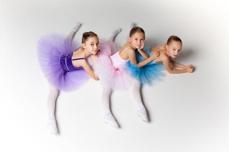 Drie kleine ballet meisjes zitten in ballet stretch in veelkleurige tutu en pointe schoenen samen op witte achtergrond