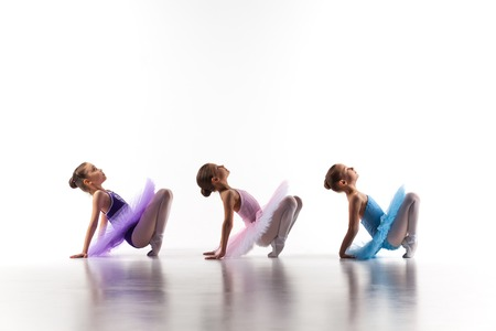 little girl dancing: Silhouettes of three little ballet girls sitting in ballet pose in multicolored tutu and pointe shoes together on white background Stock Photo