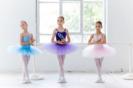 Three little ballet girls in multicolored tutu posing at ballet barre together in white studio Foto de archivo