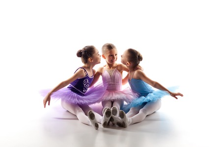 Three little ballet girls sitting  in multicolored tutu and pointe shoes together on white background