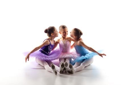 Tres niñas de ballet que se sientan en los zapatos del tutú y pointe multicolores juntos en el fondo blanco Foto de archivo