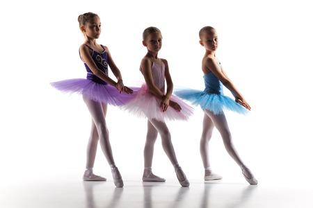 niños bailando: Las siluetas de las pequeñas bailarinas en el estudio de danza posando sobre un fondo blanco