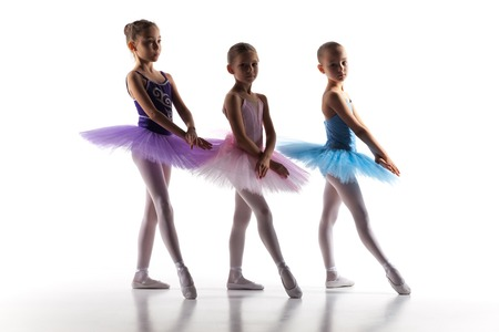 ballet child: The silhouettes of little ballerinas in dance studio posing on a white background