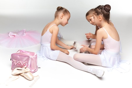 costumes: Three little ballet girls sitting in white swimsuit and pointe shoes together with cat on white background in ballet studio Stock Photo