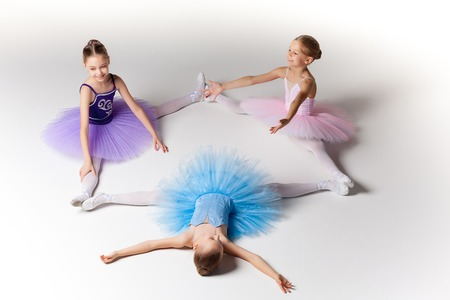 ballet: Three little ballet girls sitting  in ballet stretch in multicolored tutu and pointe shoes together on white background