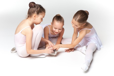 child swimsuit: Three little ballet girls sitting in white swimsuit and pointe shoes together with cat on white background in ballet studio Stock Photo