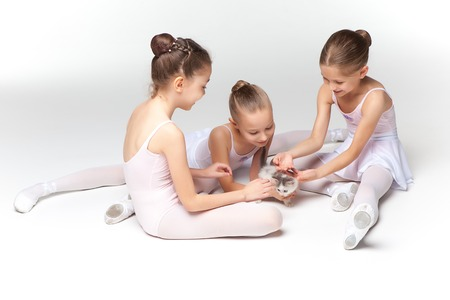 little girl dress: Three little ballet girls sitting in white swimsuit and pointe shoes together with cat on white background in ballet studio Stock Photo
