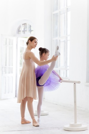 The little ballerina in tutu with personal classic ballet teacher in dance studio posing at ballet barre on a white studio background