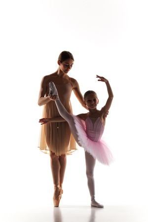 dance teacher: The silhouettes of little ballerina and personal classic ballet teacher in dance studio dancing on a white background