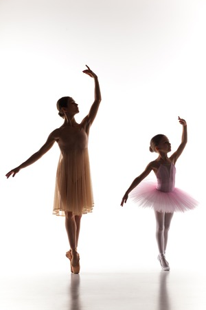 ballerina costume: The silhouettes of little ballerina and personal classic ballet teacher in dance studio dancing on a white background