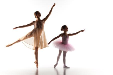 De silhouetten van de kleine ballerina en persoonlijke klassieke ballet leraar in dansstudio dansen op een witte achtergrond