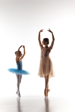 The silhouettes of little ballerina and personal classic ballet teacher in dance studio dancing on a white background