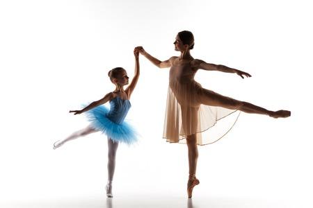 silueta humana: Las siluetas de pequeña bailarina y maestra de ballet clásico de personal en el baile estudio de baile sobre un fondo blanco