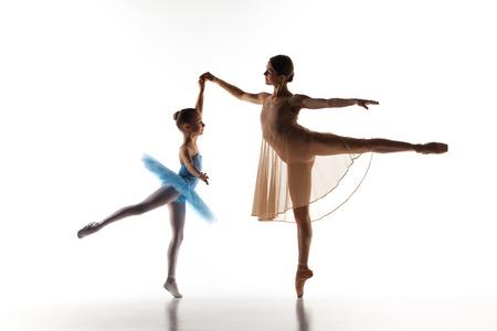 Las siluetas de pequeña bailarina y maestra de ballet clásico de personal en el baile estudio de baile sobre un fondo blanco