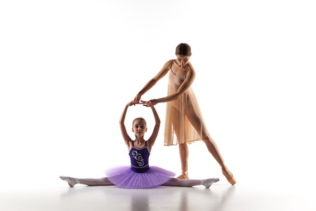 ballet silhouette: The silhouettes of little ballerina and personal classic ballet teacher in dance studio dancing on a white background