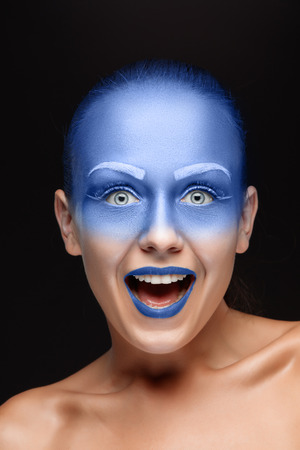 airbrushing: Portrait of a young smiling woman who is posing covered with blue paint in the studio on a black background. Girl has blue lips and white eyebrows Stock Photo