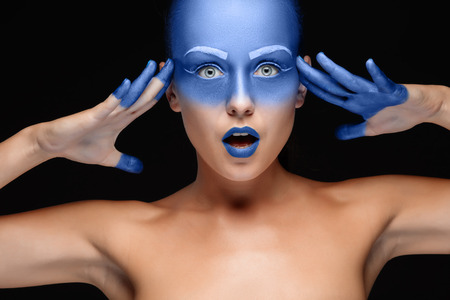 airbrushing: Portrait of a young surprised woman who is posing covered with blue paint in the studio on a black background. Girl has blue lips and white eyebrows Stock Photo