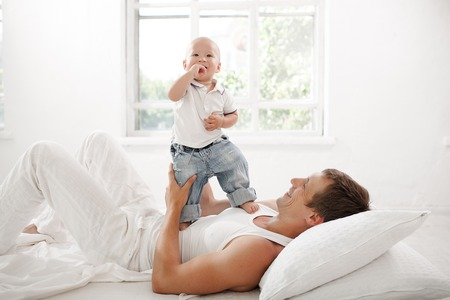 nine months: Young smiling father with his nine months old son on the bed at home on white home background