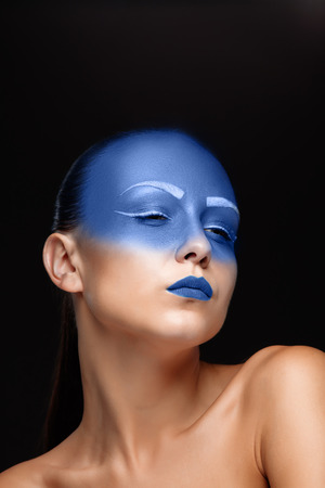 airbrushing: Portrait of a young woman who is posing covered with blue paint in the studio on a black background. Girl has blue lips and white eyebrows